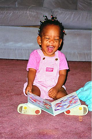 SL in Pink laughing with book